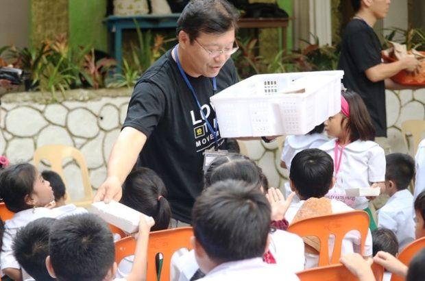 Tパエス小学校のフィーディングサービスで児童たちにお弁当を配る草原さん