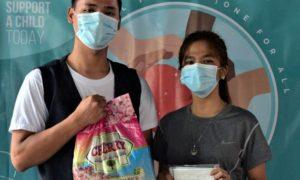 マニラ首都圏のエンチャイルド奨学生の家庭にお米を届けるキアノ・ロメロ事務局長(左)