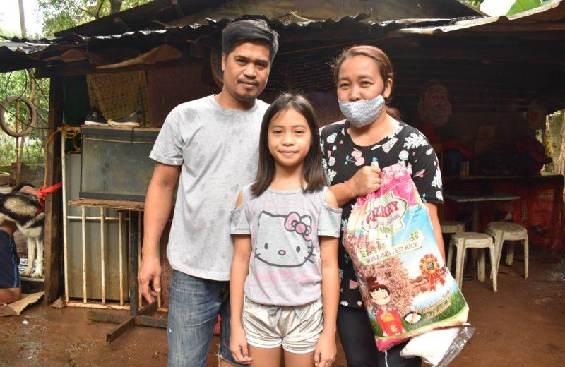 家族でお米を受け取るエンチャイルド奨学生